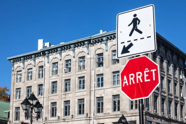 Quebec Stop Sign, obeying by bilingual rules imposing use of French language on roadsigns, translatingStop into Arret, taken in Montreal, Canada, next to a sign indicating a pedestrian crossing