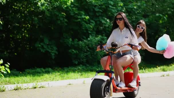 Two young and sexy arson brunette with loose hair in short denim shorts and white shirts go on an electric motorcycle in the Park, enjoying hugging each other