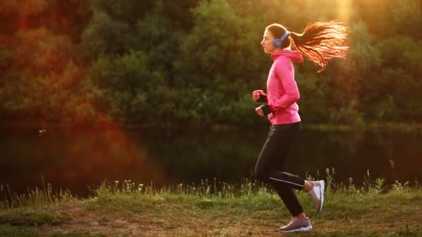 A morning jog in the Park near the pond in the Sunny rays of dawn, the girl is preparing to Mariano and lead a healthy lifestyle