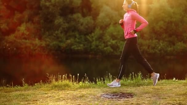 Brunette with long hair in headphones runs along the river in the Park in the morning at sunrise in the summer in a pink jacket and black pants