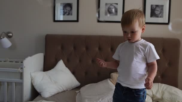 A boy in a white T-shirt and blue jeans catches soap bubbles standing on the bed in the parent bedroom