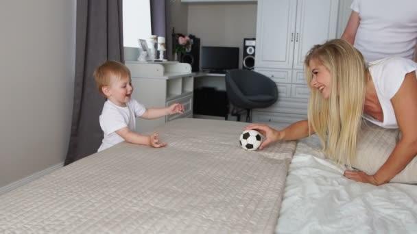 Táta s mámou hrát s chlapcem na posteli s míčem