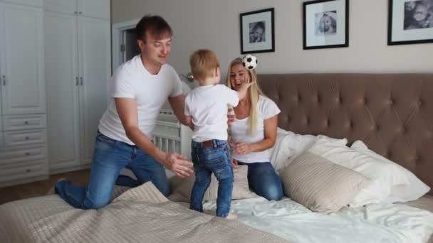 Mamma e padre solletico suo figlio. persone, famiglia, concetto di divertimento e mattina - felice del bambino con i genitori solletico nel letto di casa. Famiglia felice di trascorrere del tempo insieme a coricarsi giocando e che abbracciano