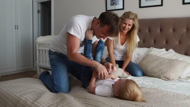 Máma a otec lechtání její dítě. lidé, Rodina, zábava a ranní koncept - šťastné dítě s rodiči lechtání v posteli doma. Šťastná rodina trávit čas spolu v spaním hraní a objímání