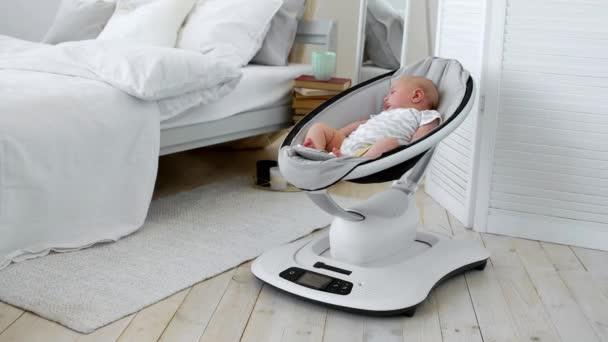 Dítě spí v houpací křeslo pro děti high-tech design v bílé ložnici