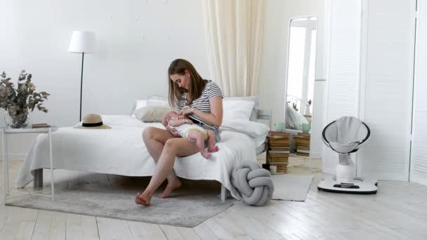 Mladá matka drží své novorozené dítě. Mami baby ošetřovatelství. Žena a nově narozené chlapce relaxovat v bílé ložnici. Krmení dítěte matka prsu. Rodina doma