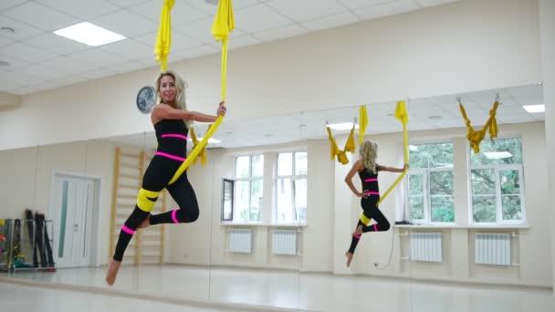 Fiatal gyönyörű nő csinál légi jóga fitness Club lila függőágy.