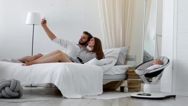 jonge ouders zittend op een bed in een wit slaapkamer nemen van een selfie met een