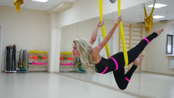 The girl is engaged in Aero yoga in the white Studio flying over the floor on the canvases in slow motion