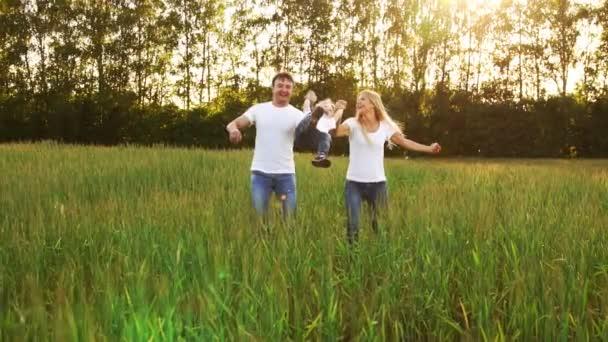 glückliche Familie: Vater, Mutter und Sohn laufen in weißen T-Shirts auf das Feld
