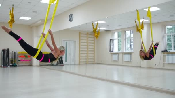 The concept of sports for a healthy lifestyle. The girl has been aerology of antigravity relaxes and swings on the canvas in a white room
