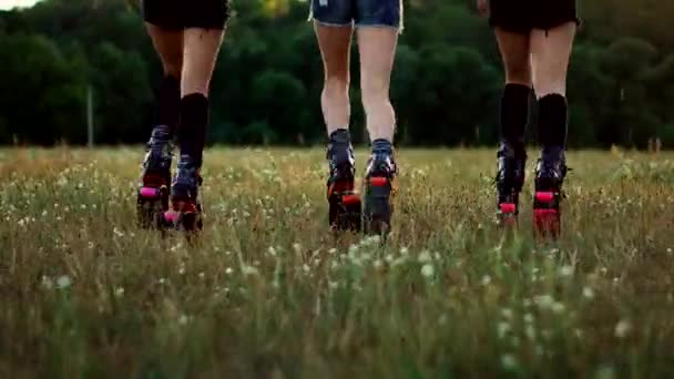 Tři dívky v botách s prameny běh přes letní Park při západu slunce, sportování