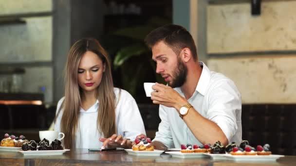 Mladý muž, ukazující na dívky telefon při rezervaci online a diskusi, mužské a ženské kolegové komunikace na přestávky na kávu kontrolu aktualizována na webové stránce vzdělání přes smartphone
