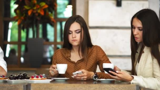 Multi-ethnic group of young friends talking and using smartphones apps on wifi in cafe, happy millennial people having fun with phones sharing coffee house table enjoying meeting in public place.