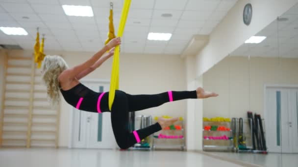 Fly yoga in a white gym. Gymnastics performs physical exercises for fly yoga, pilates, restorative health