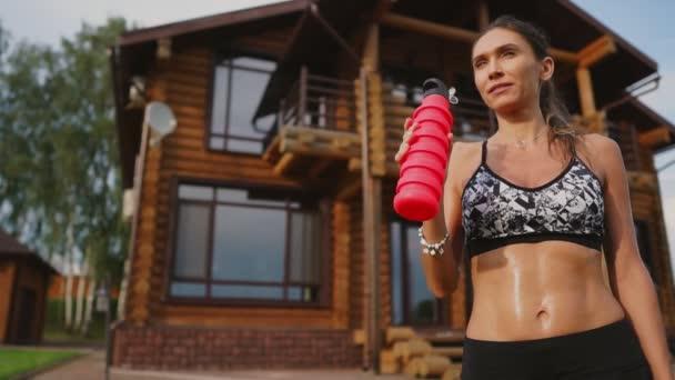 Křivý brunetka s nahuštěné stiskněte svaly a černé kraťasy, pít protein po tréninku na ulici na pozadí obrovského domu s velkými okny