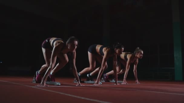 Female athletes warming up at running track before a race. In slow motion