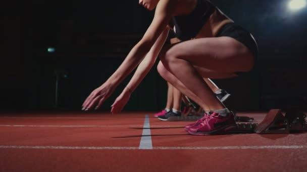 Női sportolók bemelegítés futás pályán a verseny előtt. A lassú mozgás