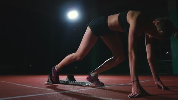 Spanyol női sportoló képzés a futópályán, a sötétben. Lassú mozgás