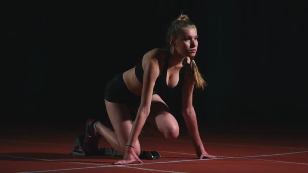 Female athlete on a dark background to run the sprint of the cross country pad on the treadmill on a dark background