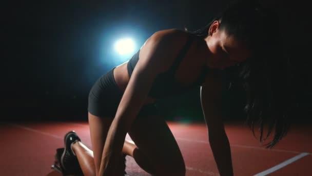 Futtatásához a sprint, a sífutó-pad a futópad a sötét háttéren sötét háttér előtt női sportoló