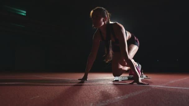 Női sportoló sötét háttér előtt arra készül, hogy futtassa a sífutó sprint a párna a futópad egy sötét háttér