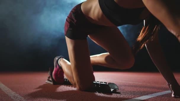 Profi női sportoló sötét háttér előtt futtatni a sprint Jogging cipő cipők a pályán, a stadion, a sötét háttér