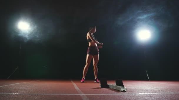 Atleta donna professionale su un fondo scuro gotovtes per eseguire lo sprint di Jogging scarpe in scarpe da ginnastica sulla pista dello stadio su uno sfondo scuro. Piano medio