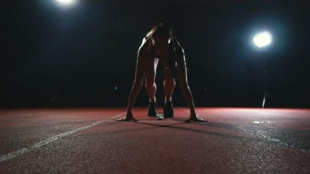 Sportoló nő fekete nadrág és egy póló-cipők a futó párna a pályán, a sport komplexum, és fuss-ban lassú mozgás