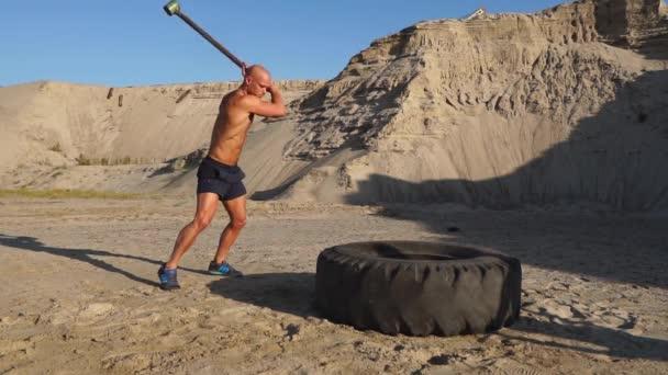 Holohlavý muž silák udeří kladivem na obrovské kolo v písečné hory ve zpomaleném filmu. sílu a vytrvalost školení pro zápasníky