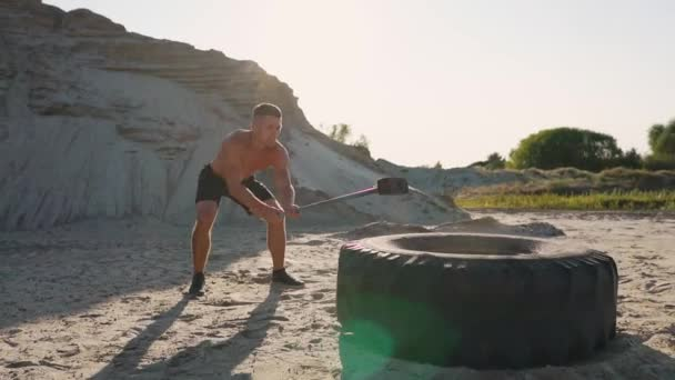 Muscle athlete strongman man hits a hammer on a huge wheel in the sandy  mountains in slow motion  strength and endurance training for wrestlers