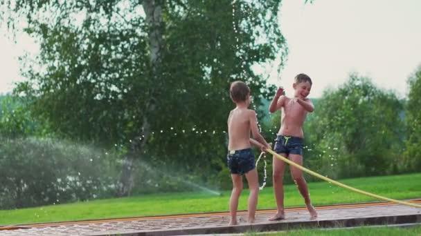 Kinder spielen im Sommer mit Wasser aus dem Schlauch Gießen