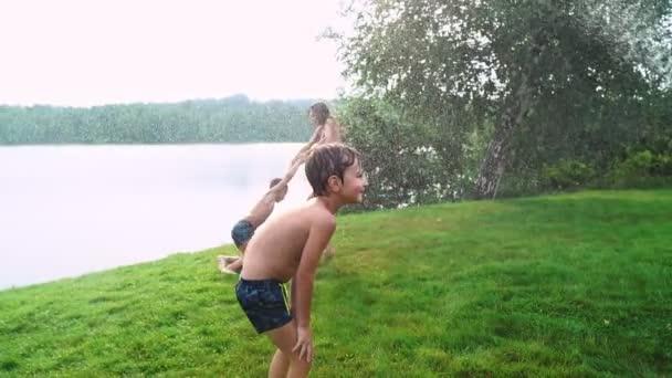 Anya apa és két fia, nyáron a fű öntötte a vizet a tömlő a gyep. Terület vidéki ház közelében egy tó naplementekor