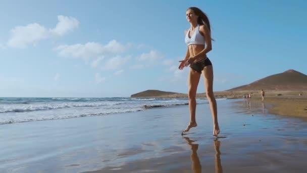 Silná žena v sportovní dělá plyometric cvičení na molu. Skok dřepy, fitness cvičení venku. Zpomalený pohyb Steadicam