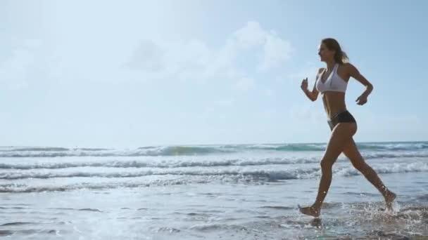 Krásná sportovní žena pobíhající po krásné písčité pláže, zdravého životního stylu, těší aktivní letní dovolenou u moře. Zpomalený pohyb Steadicam.