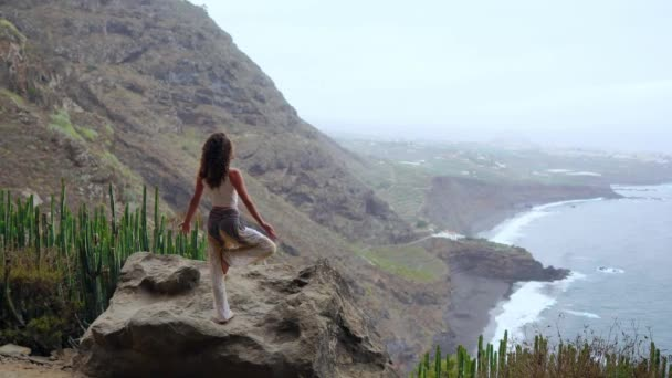 Young woman doing yoga in the mountains on an island overlooking the ocean standing on one leg raising her hands up