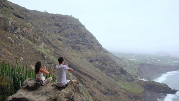 Muž a žena sedí na vrcholu hory, při pohledu na oceán, sedící na kameni meditaci pozvedá ruce a provádění relaxační dech. Kanárské ostrovy