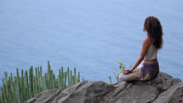 Young woman doing yoga in the mountains on an island overlooking the ocean sitting on a rock on top of a mountain meditating in Lotus position.
