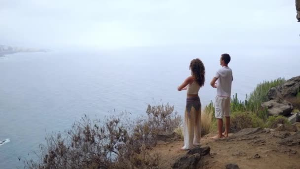 A man and a woman standing on the edge of a cliff overlooking the ocean raise their hands up and inhale the sea air during yoga