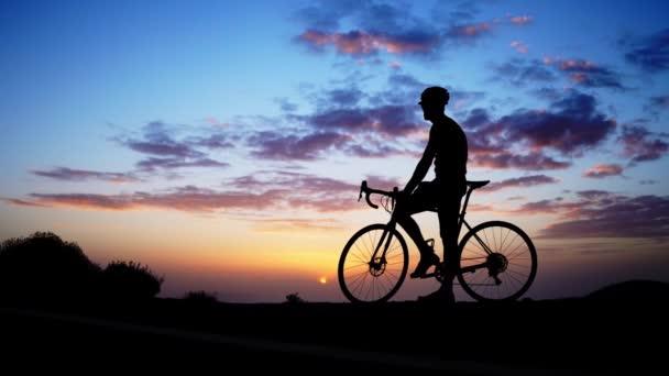 Silueta kolo Rider na skále při západu slunce
