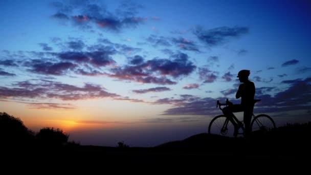 Muž na kole stojí na vrcholu hory a obdivuje na západ slunce. Kamera se pohybuje na statickou.