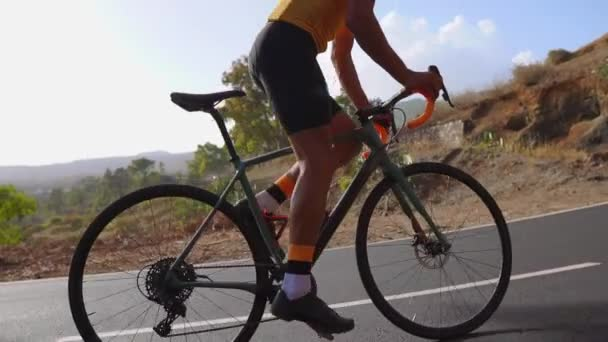 Muž na silniční kolo venkovní cvičení na prázdné silnici na kole v ranní. Extrémní sport koncept. Zpomalený pohyb