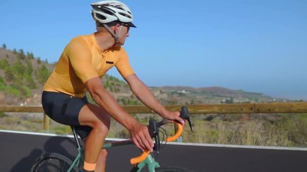 Horské kolo cyklistu jedoucího do kopce po silnici. Zadní pohled. Letní den. Zpomalený pohyb