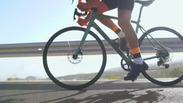 Muž na silniční kolo venkovní cvičení na prázdné silnici na kole v ranní. Extrémní sport koncept. Close - up, pomalý pohyb