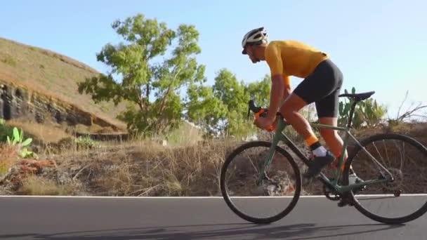 Cyklista, jízda na kole na otevřené silnici na západ slunce
