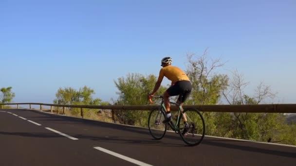 Muž se jezdit na kole na silnici. Sport a aktivní život koncepce západu slunce čas. Muž na koni na kole v parku. Modrá obloha s paprskem oranžové slunce nad tělem cyklista.
