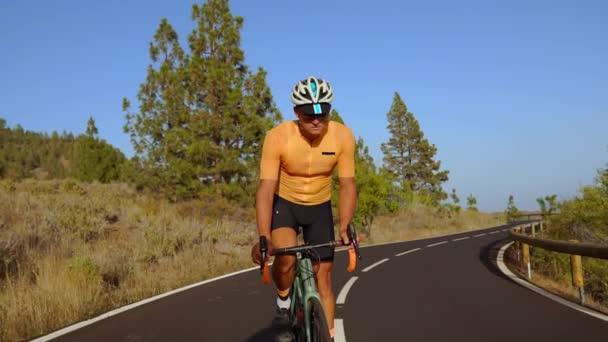 Sledovací video natočené muž cyklista lezení po horské silnici. Člověk dělá cyklistický trénink na silnici kopcovité silnice za slunečného dne.
