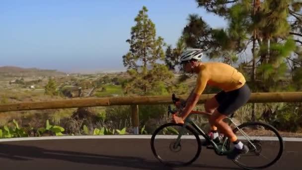 Široký úhel sledování snímku fit mužské sportovce jízdní kolo na dlouhé rovné silnici v krajině. Muž na kole na silnici rovnou dálnici.