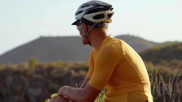 Muž cyklista odpočívá po příjezdu a obdivovat výhled na hory