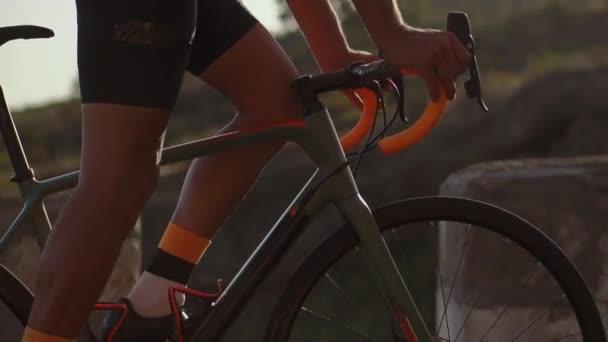 Detail cyklistu jedoucího na horské silnici v létě. Kola, volant a pedály